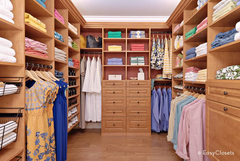 This bedroom closet boasts a matching walnut finished cabinetry and hardwood flooring.