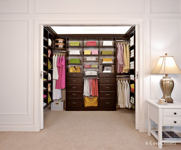 This small bedroom closet surrounded by white walls features a brown finished cabinetry set on a carpet flooring.