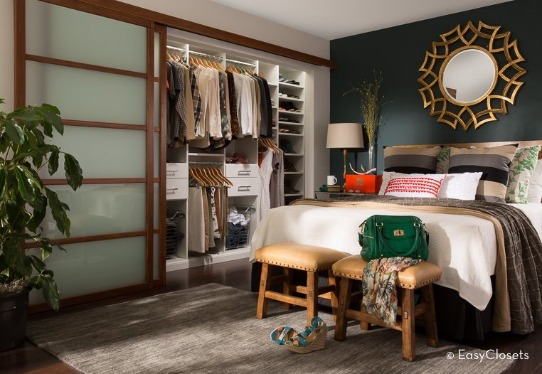 Small bedroom closet with a sliding door and a white cabinetry with its own lighting.