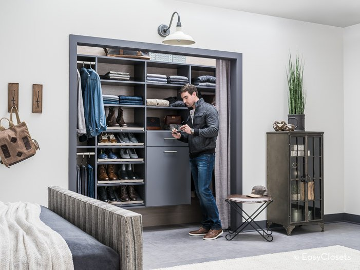 Classy modern men's closet featuring a gray tiles flooring with a white rug along with gray cabinets. The closet is located inside his bedroom.