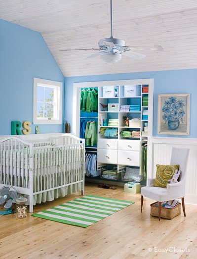 Small baby's bedroom closet with white cabinetry and shelving.