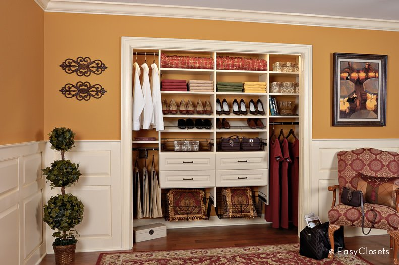 This open concept closet is located in a room with dark gold walls and several antique and ethnic objects, all with gold accents. The creamy white closet balances the warm tones and elaborate patterns of the room and reflects the beautifully contrasting characteristics of the objects inside, including modern high heels and gold-tasseled throw pillows.