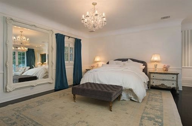 Classy guest bedroom illuminated by a glam chandelier that hung over the brown bed. It is decorated with a large ornate framed mirror mounted next to the arched window covered with blue draperies.
