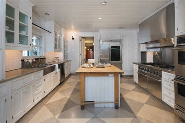 Farmhouse U-shaped kitchen with white cabinetry, stainless steel appliances, and a kitchen island with wood surface standing in the middle of the room.