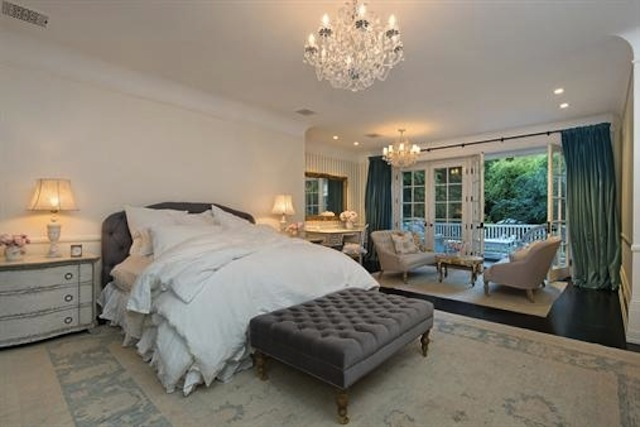 Deluxe primary bedroom boasts a gray tufted bed with a matching ottoman on its end along with a seating area by the glass doors that open to the balcony. It is lighted by crystal chandeliers and table lamps that sit on distressed white nightstands.