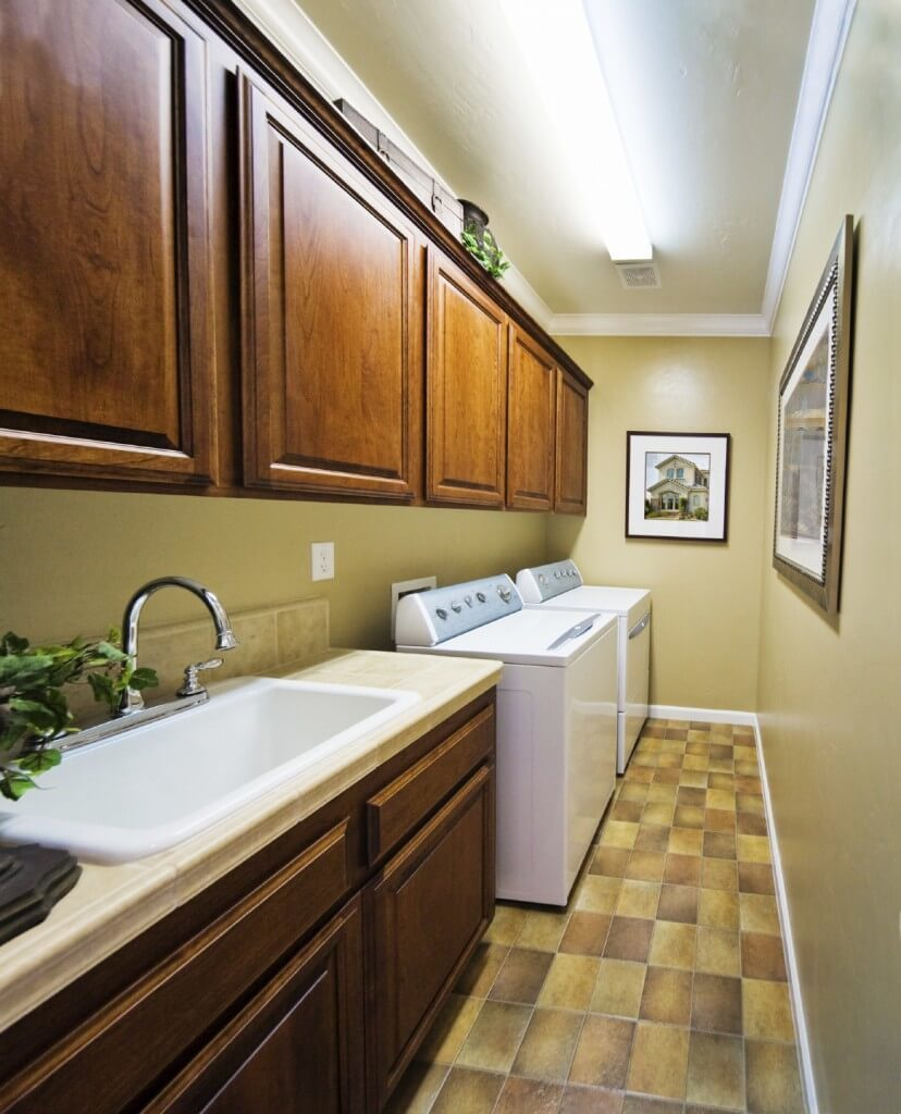 This laundry room boasts classy tiles flooring and a gorgeous sink counter matching the brown cabinetry just above it.
