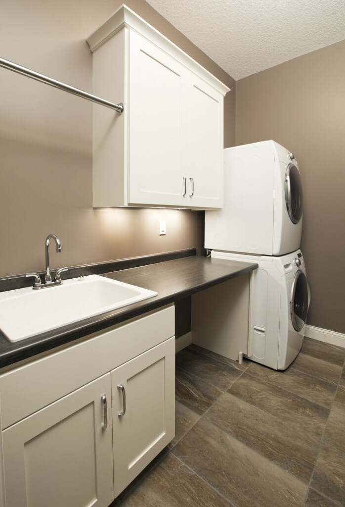 This laundry room features a sink counter and white cabinetry, along with gray walls and stylish tiles flooring.