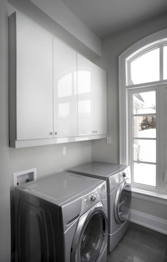 A stylish set of washer and dryer on top of the room's stylish tiles flooring.