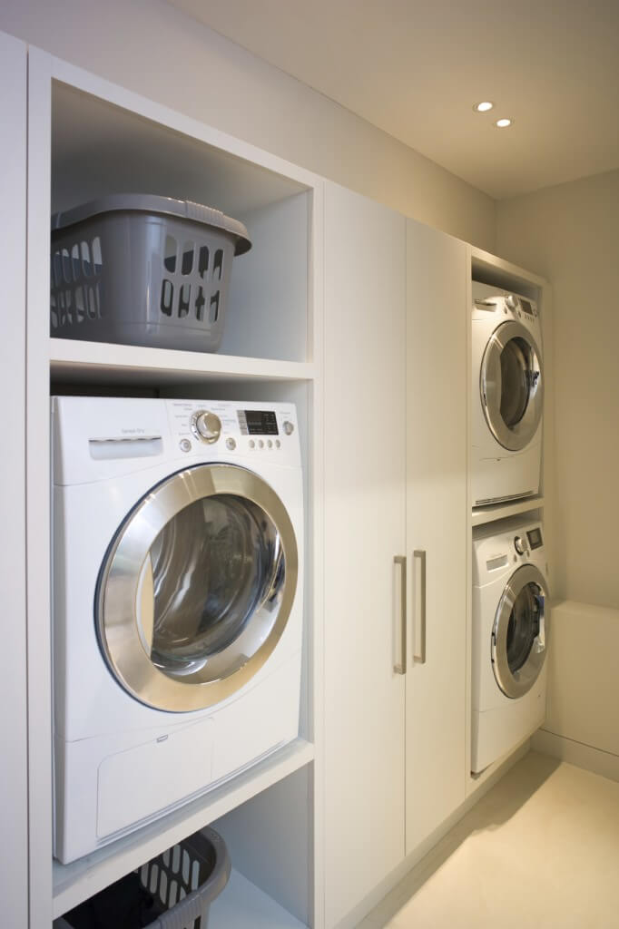A laundry room boasting built-in washer and dryer housing and cabinetry.