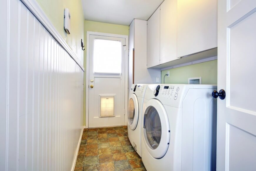 This laundry room is set in the home's mudroom featuring classy tiles flooring.