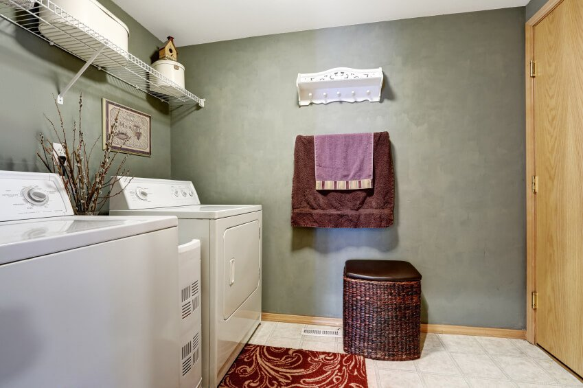 A medium-sized laundry area featuring gray walls and white tiles flooring.