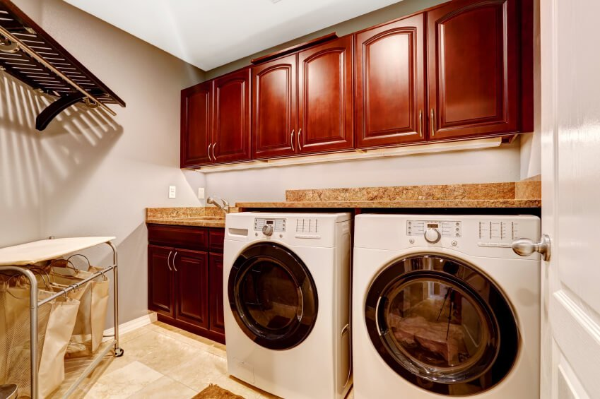 A laundry room with a washer and dryer combo along with reddish-finished cabinetry and counter.