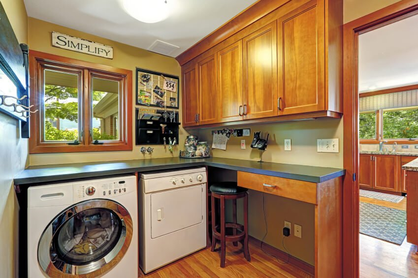 A cozy laundry room set up beside the home's kitchen. it features a counter and desk combo with black countertop.