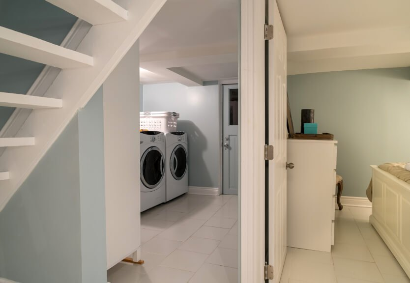 A laundry room featuring a large washer and dryer combo set on the room's white tiles flooring.
