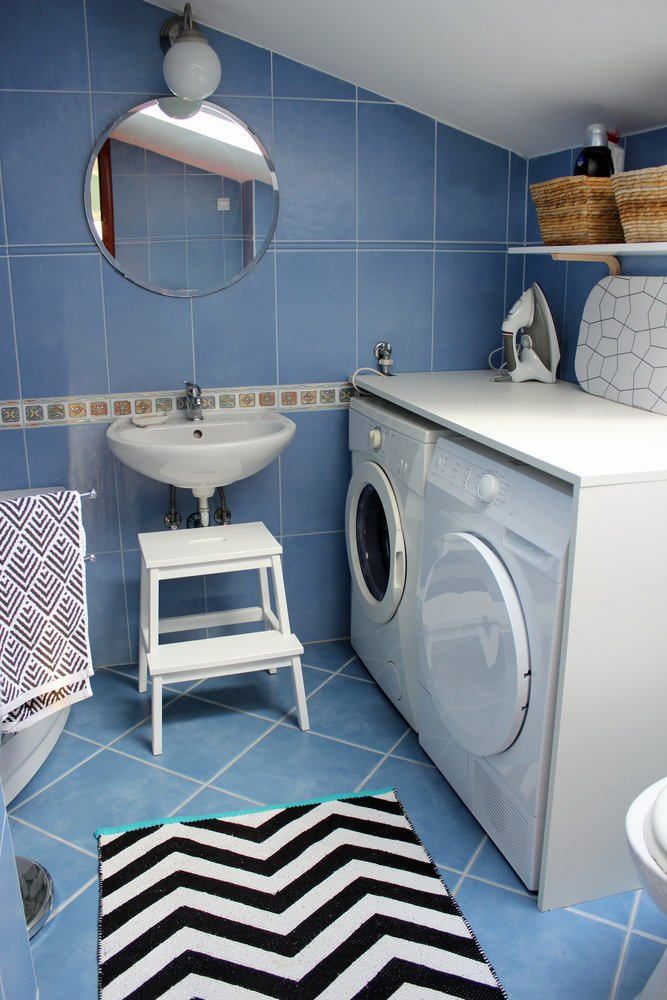 Blue-tiled laundry room with white washer and dryer combo.
