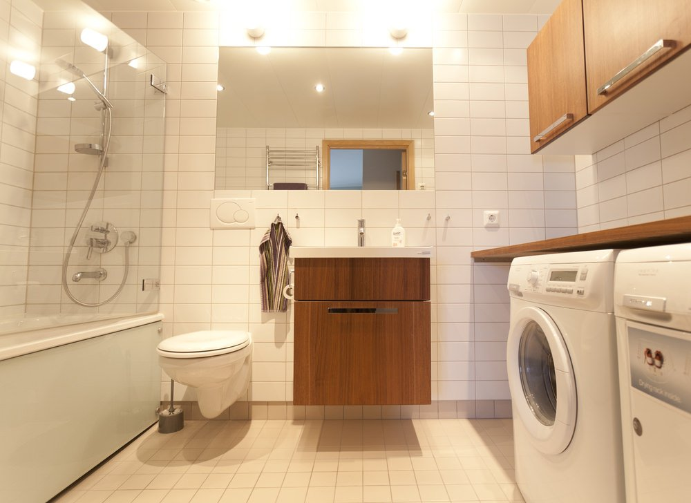 A bathroom and laundry combo featuring white washer and dryer matching the white tiles flooring and walls.