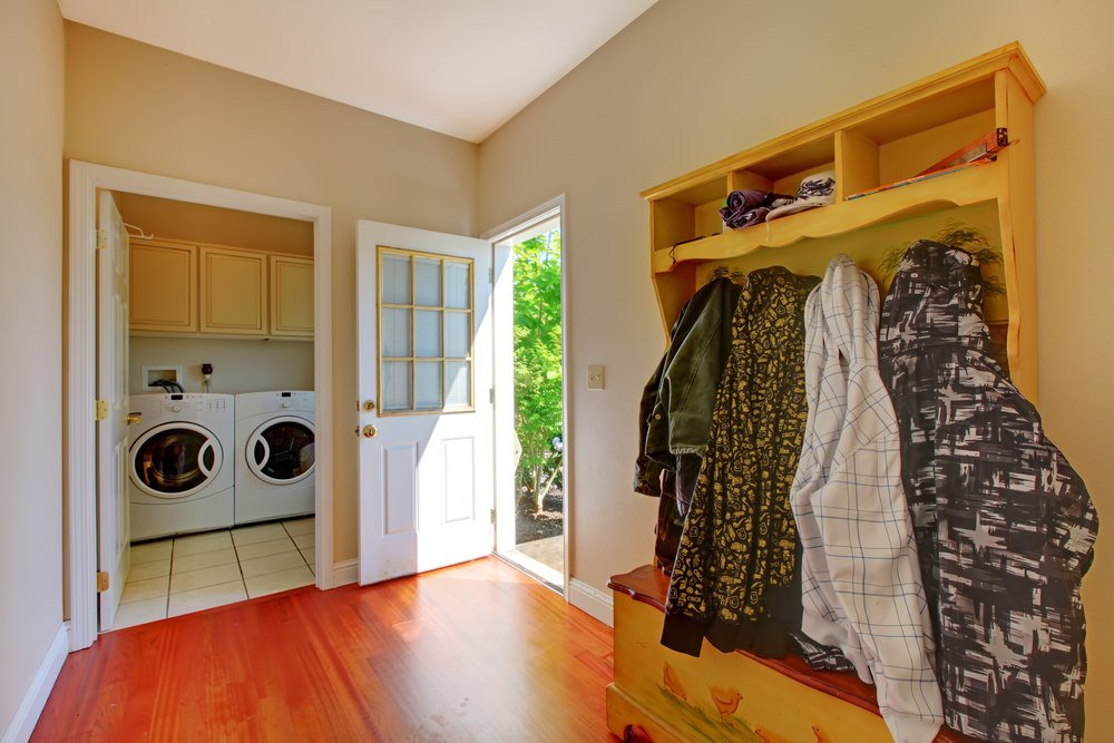 A laundry room set in the home's mudroom featuring tiles flooring and walnut-finished cabinetry.