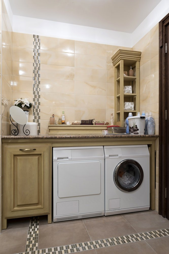 A classy laundry room with tiles flooring and walls. The counter features a granite countertop.