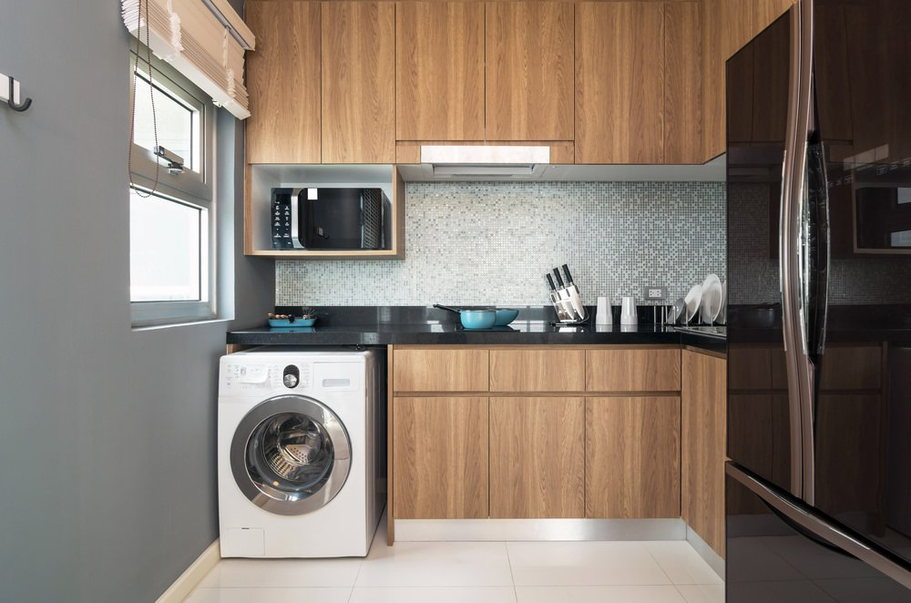 A Modish Laundry Room And Kitchen Set Up Featuring Cherry Finished Cabinetry Counters Along
