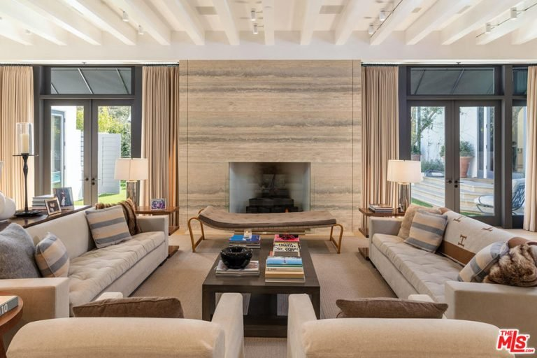 This living room offers tufted seats and a wooden coffee table that faces the fireplace in between double glass doors covered with beige draperies.