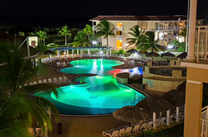 Gorgeous swimming pool with fancy colorful lights features a poolside pergola filled with white lounge chairs.