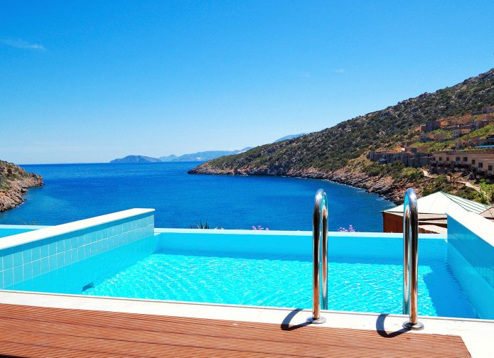 A sparkling swimming pool with stainless steel handrails overlooks the stunning ocean and hills that are filled with houses.