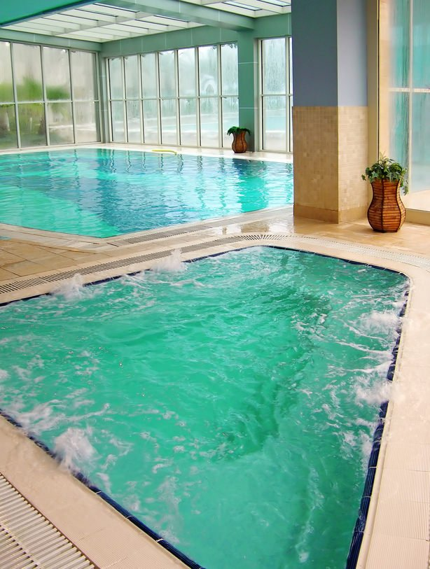 An indoor pool with a separate jacuzzi enclosed in full height glazing and green ceiling fixed with series of skylights allowing plenty of natural light in.
