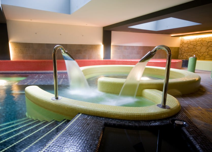 An indoor pool clad in black mosaic tiles and accented with yellow tubs mounted with a pair of stainless steel shower sprays that serve as waterfall fountain.