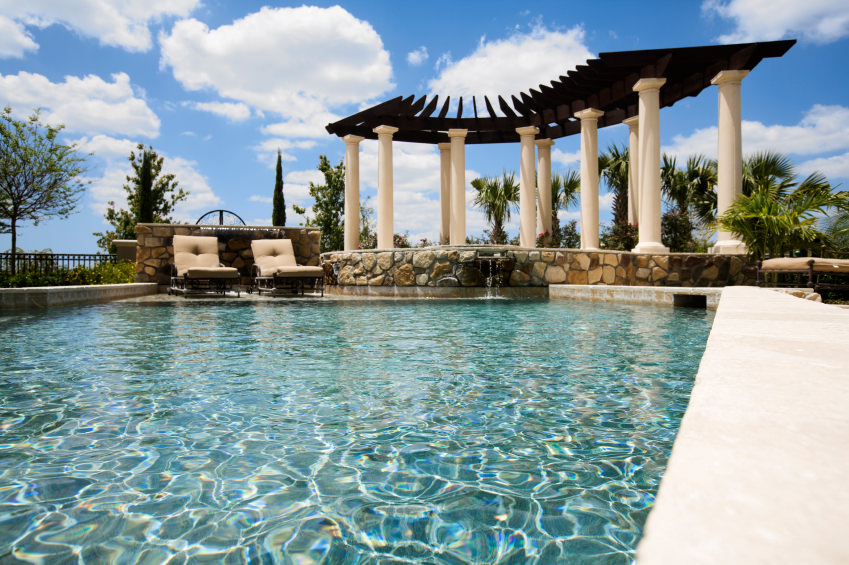 A sparkling swimming pool with a pair of tufted lounge chairs beside the two-tone pergola that's framed with Greek columns.