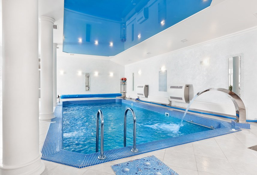 White indoor swimming pool with a tray ceiling mirroring the blue water from the pool.