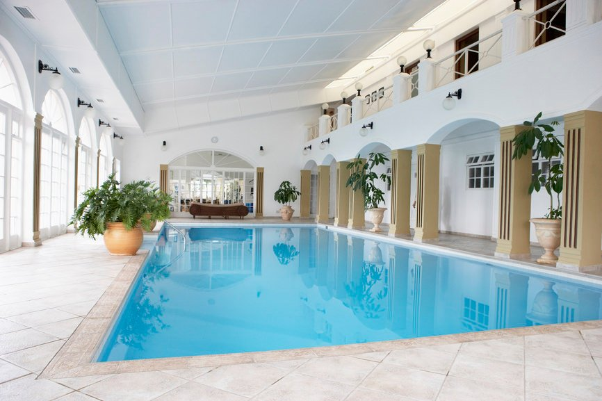An in-ground pool lined with tan columns forming arches and accented with beautiful potted plants that refresh the area.