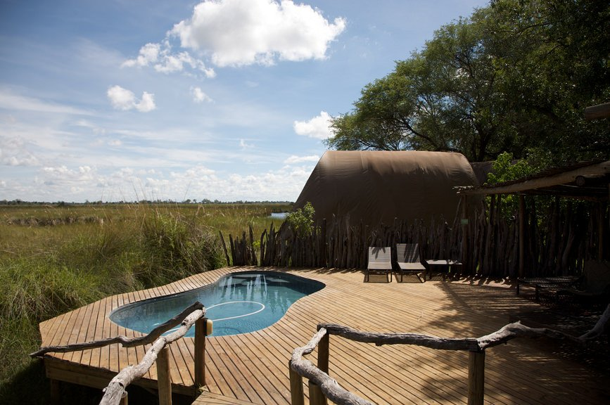 A kidney-shaped pool fitted on the floating wooden deck with a bridge that's framed with natural wood railings. It includes lounge chairs next to the rustic cabana.