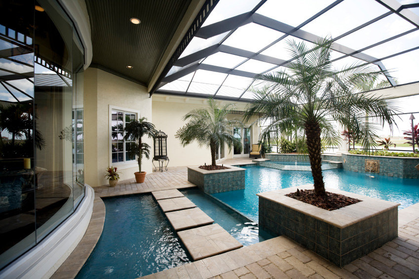 This luxury house boasts a screened-in pool with concrete pathway and planters that are filled with palm trees and plants.