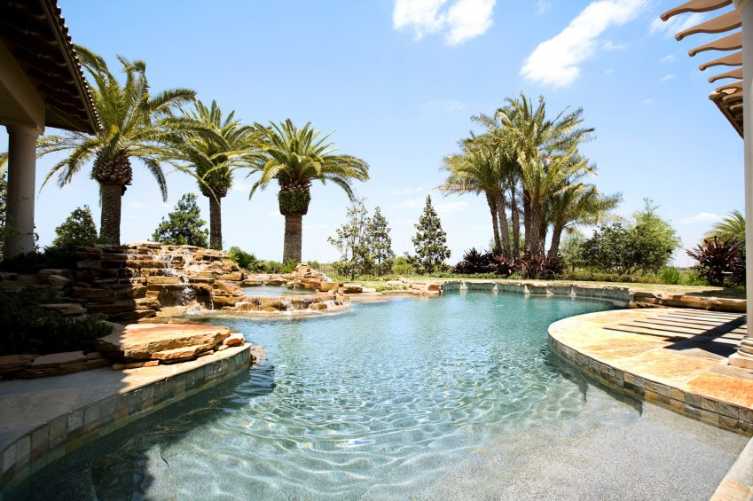 A gorgeous swimming pool highlighting a waterfall feature next to the stone hot tub surrounded with lovely palm trees and plants.