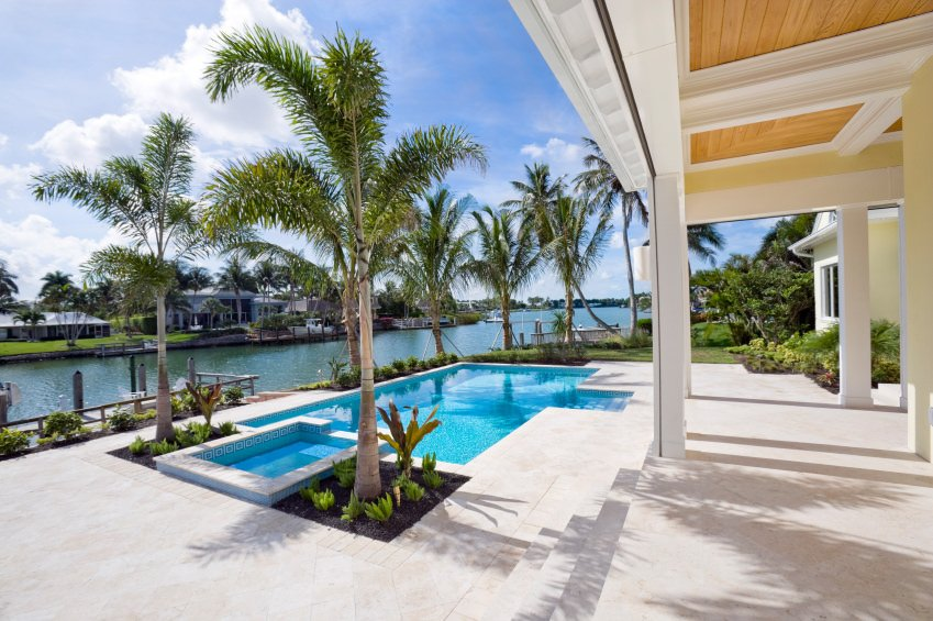 A backyard pool surrounded by palm trees and plants. It overlooks a stunning river just beside the house.