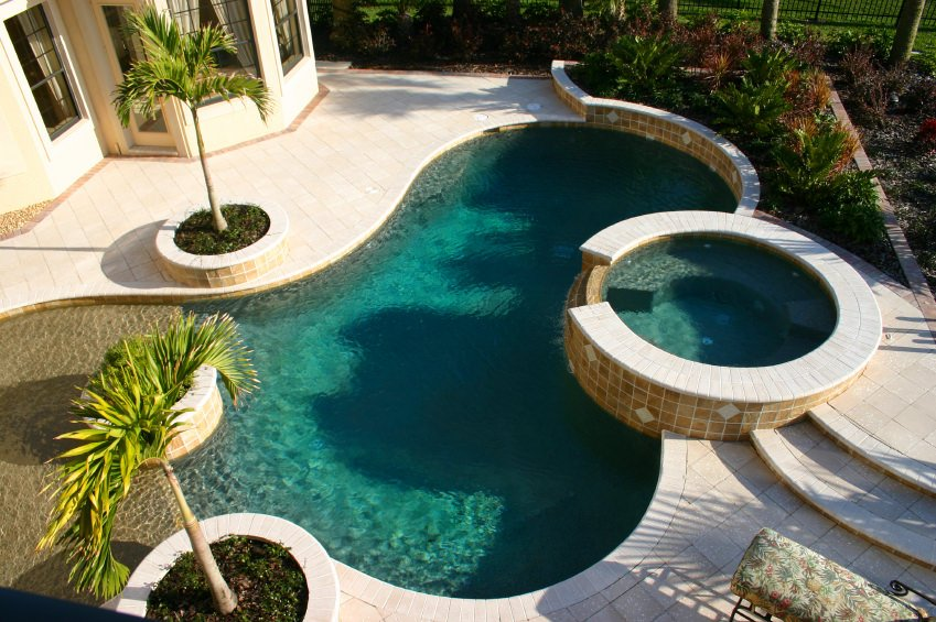 This house features a gorgeous swimming pool accompanied by a jacuzzi and lovely palm trees on round planters.