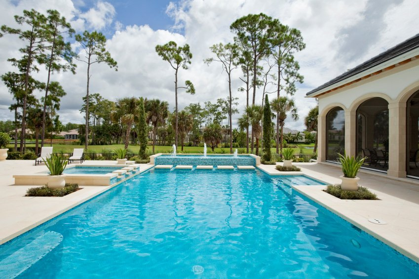 A closeup look at this luxury swimming pool highlighted with a water feature at the far end.