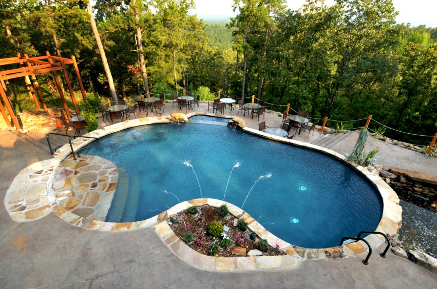 A kidney-shaped pool with enchanting forest view lined with stone surround tiles. It offers water features and multiple seating.