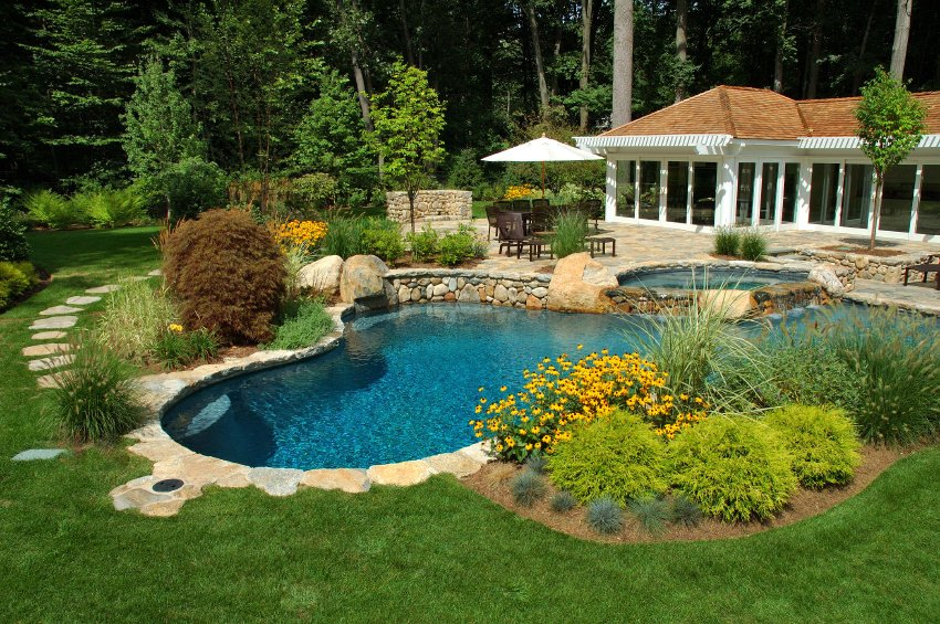 A white pool house surrounded with full height glazing and offers a curved pool with hot tub. It is accented with lovely plants and lush lawn with a stone pathway leading to the patio.