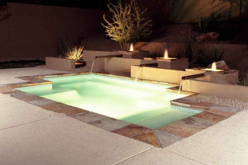 A luminous pool on a night setting showcasing water features attached to the fire pits.