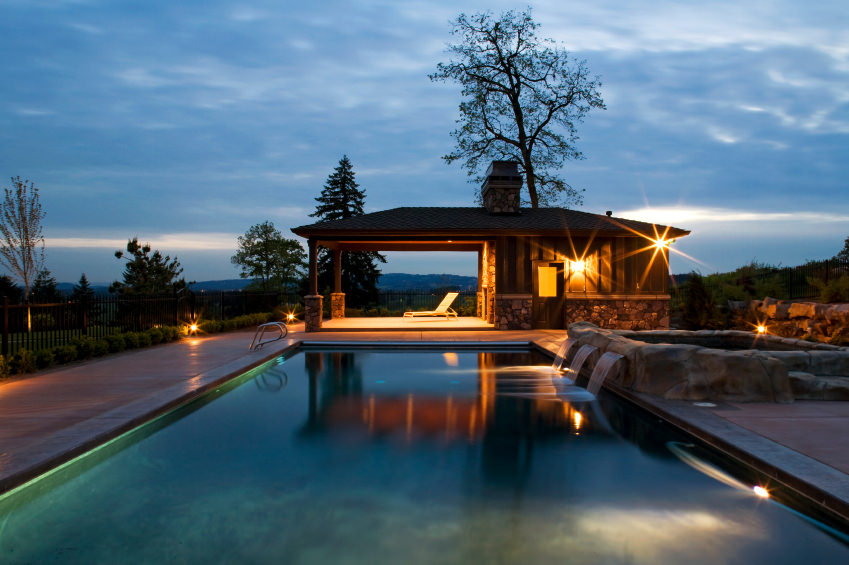 A stunning swimming pool during nighttime offering a cabana with lounge chair. It has waterfall features coming out from the stone hot tub beside the pool.