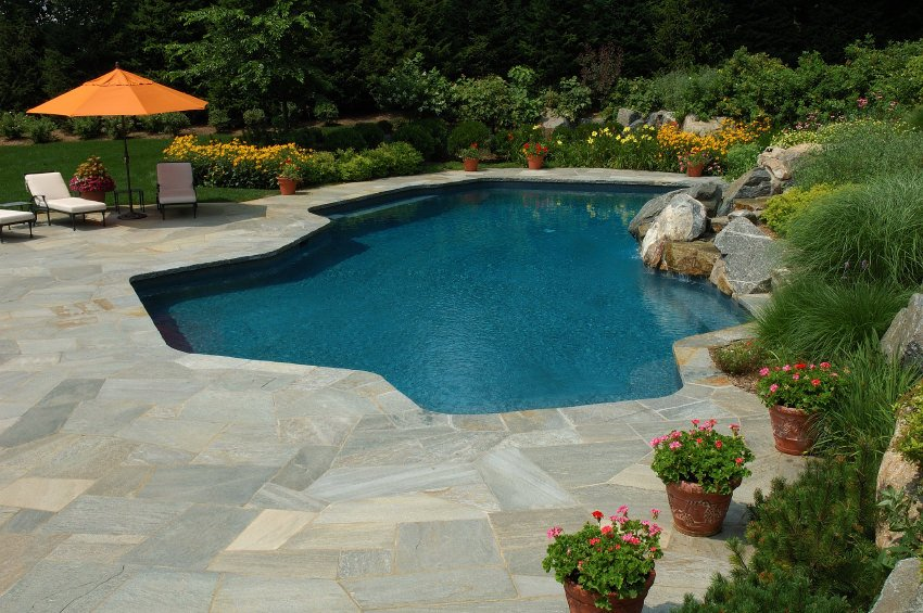 A freeform pool in the middle of a lush green garden accented with natural stones and colorful flowers. It has a stone deck and white seats.