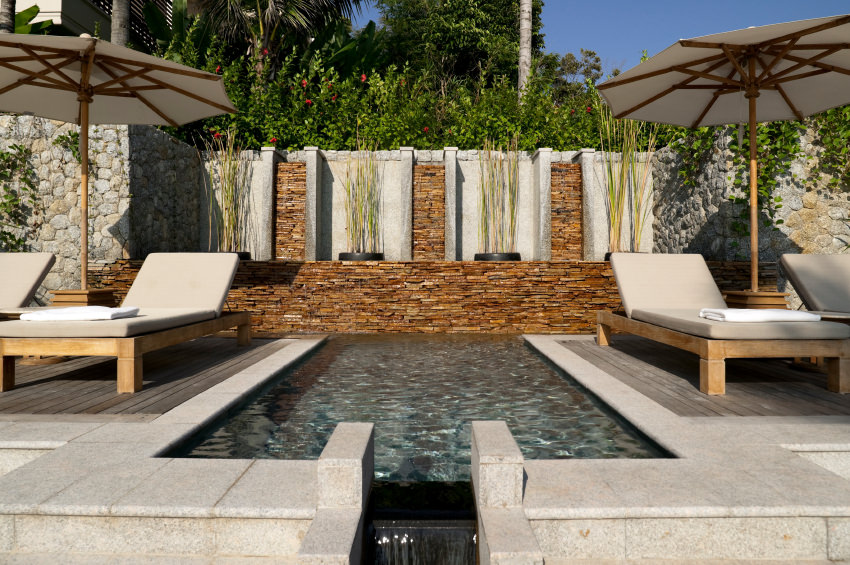 A stunning pool in between wood plank decks filled with gray lounge chairs. It includes stacked stone walls lined with tall plants providing a lovely background.