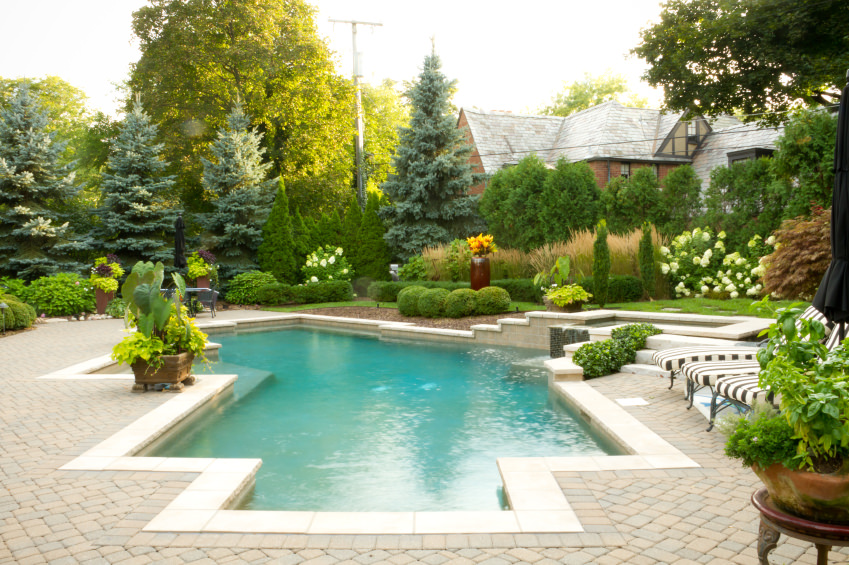This swimming pool is situated in the middle of the majestic garden filled with manicured shrubs and bushes along with pine trees and striped lounge chairs.