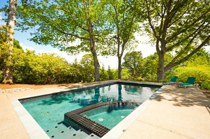 A pair of lounge chairs complements with the gorgeous swimming pool surrounded with abundant plants and trees.