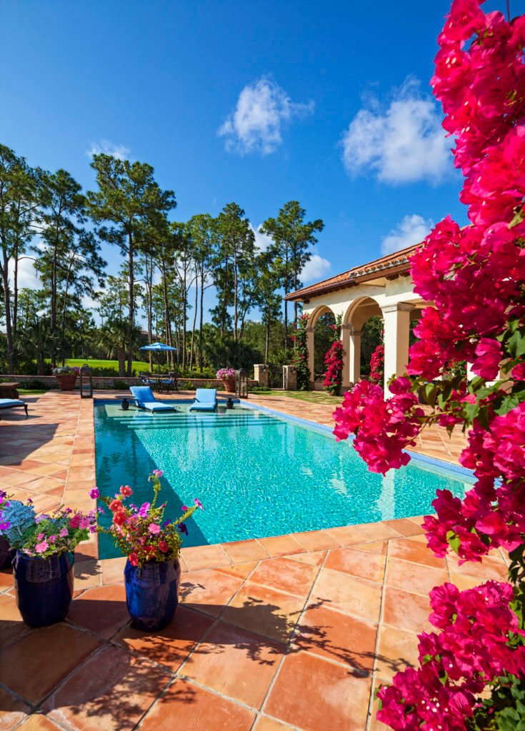 A backyard full of lovely and colorful flowers along with a rectangular swimming pool offering a pair of blue lounge chairs that sit on the first step of the pool.