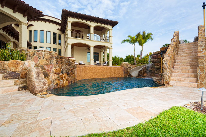 A deluxe two-story house features a gorgeous pool framed with stone retaining walls that are accented by bricks along with a slide and waterfall.