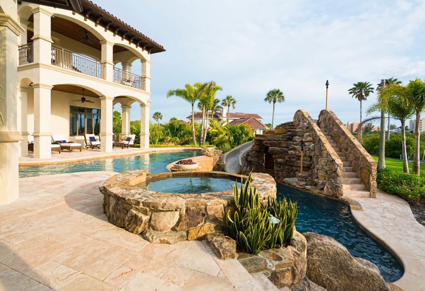 A luxurious house showcases a sparkling pool with jacuzzi and slide. There are tropical trees and plants in the background that give serene vibes.