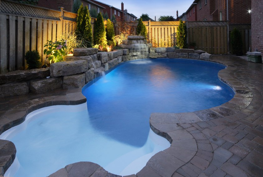 A curved swimming pool boasts a retaining wall with water features and complements with the stone deck. There are plants behind it surrounded by a wooden fence.