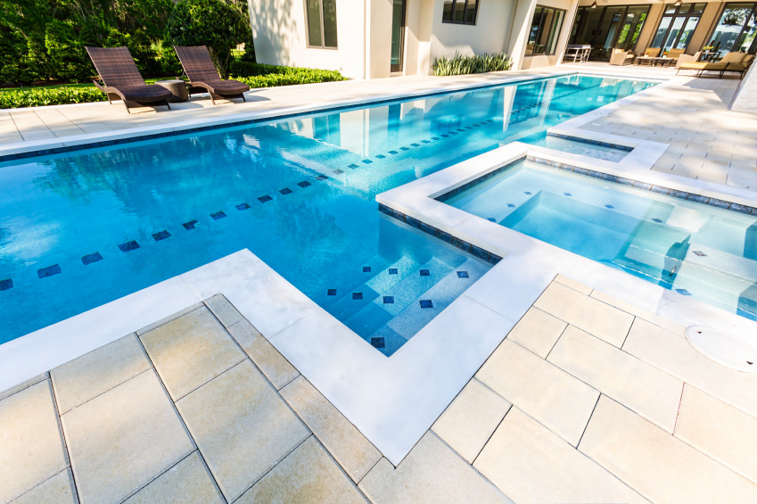 A modern house offering an in-ground lap pool with brick deck and rattan lounge chairs.